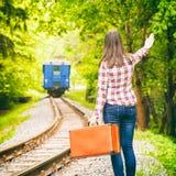 Abreisezug, junge Frau, die seine Hand wellenartig bewegt Stockfoto