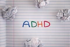 Abreviatura ADHD na folha do caderno com algum bal amarrotado do papel Foto de Stock