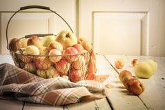 Abricós e maçãs frescos saborosos maduros na cesta tecida do metal Imagens de Stock