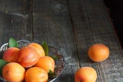 Abricots dans une cuvette sur le fond en bois photographie stock libre de droits