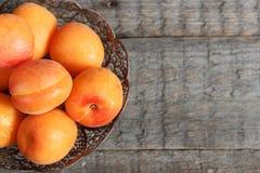 Abricots dans une cuvette sur le fond en bois photos stock