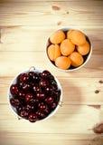 Abricots et baies frais de cerises sur le fond en bois Image stock