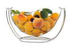 Abricots et cerises mûrs dans un panier métallique sur un fond blanc Photographie stock libre de droits