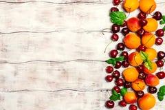 Abricots et cerises sur le fond rustique image libre de droits