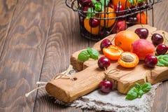 Abricots et cerises sur le fond rustique photographie stock libre de droits