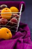 Abricots et prunes dans un casier métallique avec la soie pourpre drapée sur un fond en soie bleu avec l'espace de copie Photographie stock