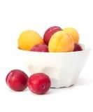 Abricots et prunes mûrs dans la cuvette blanche photos libres de droits