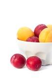 Abricots et prunes mûrs dans la cuvette blanche photographie stock