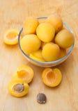 Abricots mûrs dans le bol en verre sur le conseil en bois photos libres de droits