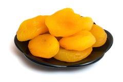 Abricots secs d'un plat noir, image sur un background_ d'isolement blanc photos libres de droits
