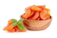 Abricots secs dans une cuvette en bois avec les feuilles en bon état d'isolement sur le fond blanc Photo stock