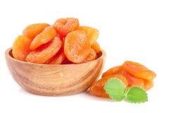 Abricots secs dans une cuvette en bois avec les feuilles en bon état d'isolement sur le fond blanc Photos libres de droits