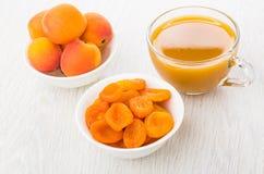 Abricots secs et frais dans des cuvettes, tasse avec du jus d'abricot Images libres de droits