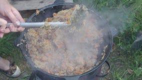 Abriendo el pote y el stirring de Kazán el pilaf en el horno al aire libre almacen de metraje de vídeo