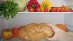Abriendo la puerta del refrigerador, una mano femenina pone metrajes