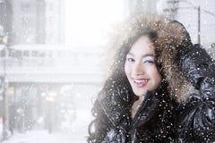 Abrigo de invierno que lleva de la muchacha alegre en día nevoso Foto de archivo libre de regalías