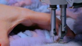 Abrigo de pieles de costura del sastre con la máquina de coser almacen de metraje de vídeo