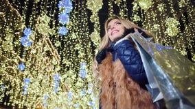 Abrigo de pieles que lleva sonriente atractivo de la mujer con el bolso de compras de la Navidad en el fondo de las luces ámbar metrajes
