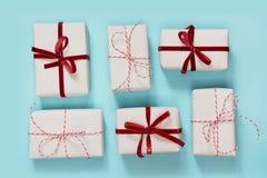 Abrigo de varios regalos de la Navidad en papel decorativo con el arco rojo laing en azul Endecha plana Visión superior imágenes de archivo libres de regalías