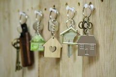 Abrigue a chave com o keyring home de madeira que pendura no fundo de madeira da placa, conceito da propriedade, espaço da cópia imagens de stock royalty free