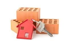 Abrigue a chave da porta com o pendente e os tijolos vermelhos da porta-chaves da casa Imagens de Stock Royalty Free