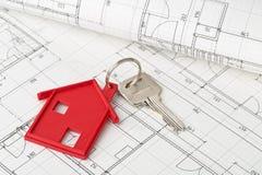 Abrigue a chave da porta com o pendente vermelho da porta-chaves da casa no plano da construção Imagens de Stock Royalty Free