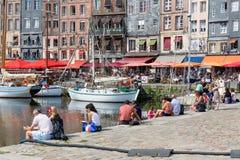 Abrigue a cidade Honfleur com os navios de navigação amarrados e os povos de relaxamento Foto de Stock