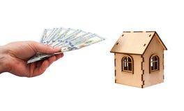 Abrigue a forma feita de blocos e do dólar de madeira das moedas com mão do homem Foto de Stock Royalty Free