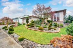 Abrigue o exterior com gramado bem mantido e desing ajardinando agradável Fotografia de Stock Royalty Free