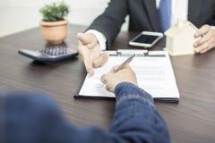 Abrigue o sinal do comprador e escreva-o no seguro da casa do contrato fotos de stock royalty free