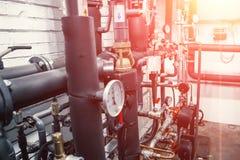 Abrigue o sistema de aquecimento com muitos tubulações de aço, manômetros e tubos do metal fotografia de stock royalty free