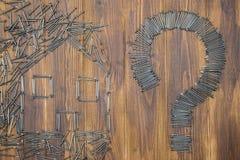 Abrigue a pergunta do reparo, grupo de prego no fundo de madeira Foto de Stock
