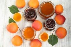 Abrikoos en bessenjam in kruiken met rijp sappig fruit Royalty-vrije Stock Foto