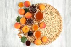 Abrikoos en bessenjam in kruiken met rijp sappig fruit Stock Afbeelding
