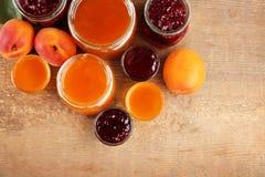 Abrikoos en bessenjam in kruiken met rijp sappig fruit Stock Foto's