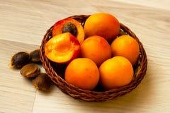 Abrikozen in een mand en een paar netto abrikozenpitten royalty-vrije stock foto