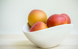 Abrikozen in witte kom Royalty-vrije Stock Afbeeldingen