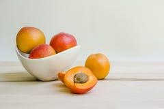 Abrikozen in witte kom met open abrikoos Stock Afbeelding