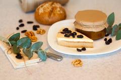Abrikozenjam in de glaskruik en het stuk van smakelijke cake Royalty-vrije Stock Afbeeldingen