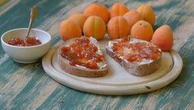 Abrikozenjam die op brood met abrikozen op achtergrond wordt uitgespreid Royalty-vrije Stock Afbeelding
