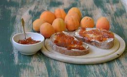 Abrikozenjam die op brood met abrikozen op achtergrond wordt uitgespreid Royalty-vrije Stock Foto