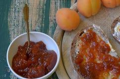 Abrikozenjam die op brood met abrikozen op achtergrond wordt uitgespreid Royalty-vrije Stock Afbeeldingen
