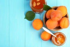 Abrikozenjam in kruiken met lepel en rijp sappig fruit Royalty-vrije Stock Afbeelding