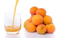 Abrikozensap in een glas dichtbij een hoop van abrikozen wordt gegoten die Royalty-vrije Stock Afbeelding