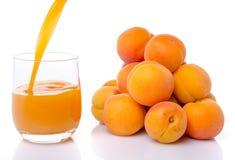 Abrikozensap in een glas dichtbij een hoop van abrikozen wordt gegoten die Royalty-vrije Stock Afbeeldingen