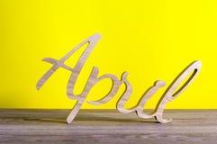 Abril - palabra tallada de madera en fondo amarillo Tiempo de primavera, 1r de abril - Pascua y día de los tontos Fotos de archivo
