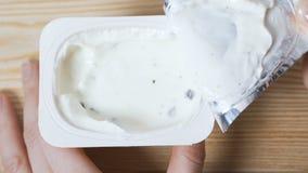 Abrindo um frasco do iogurte filme