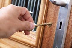 Abrir una puerta con un clave de la casa Imagen de archivo libre de regalías