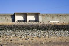 Abritez et banc le long du mur de mer, Canvey Island, Essex, Angleterre Photos stock