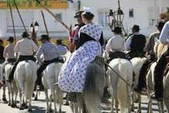 Abrivado, Saintes Maries de la Mer, Camargue, France. Gardians horseback riding to the arena with few women at their back, during the summer festival of Abrivado Stock Image